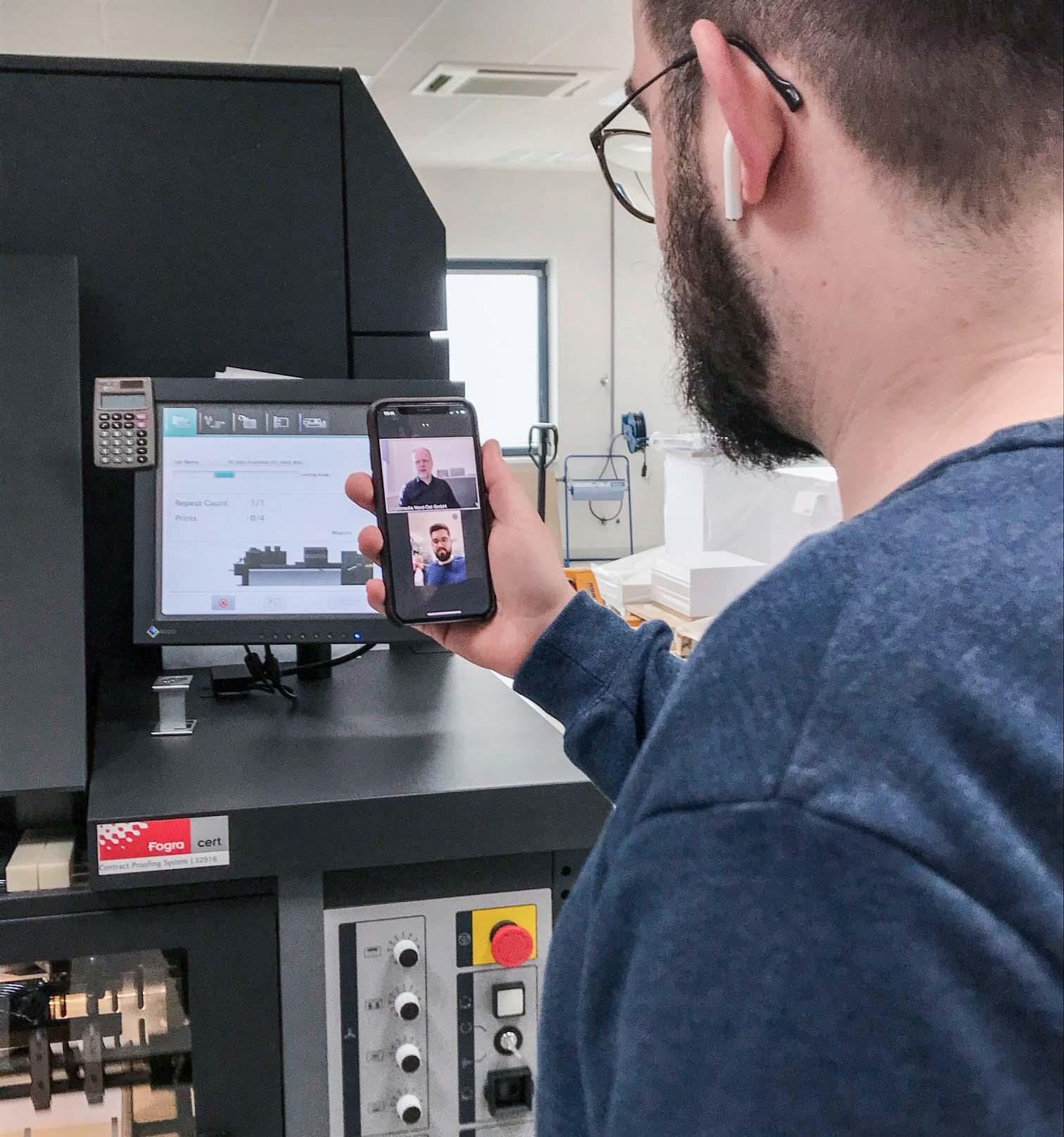 Lars Holscher von der Wegner GmbH steht beim QSD-Audit an der Druckmaschine und hält ein Smartphone in der Hand, über welches der Prüfer Udo Eickelpasch jeden Schritt mitverfolgen kann