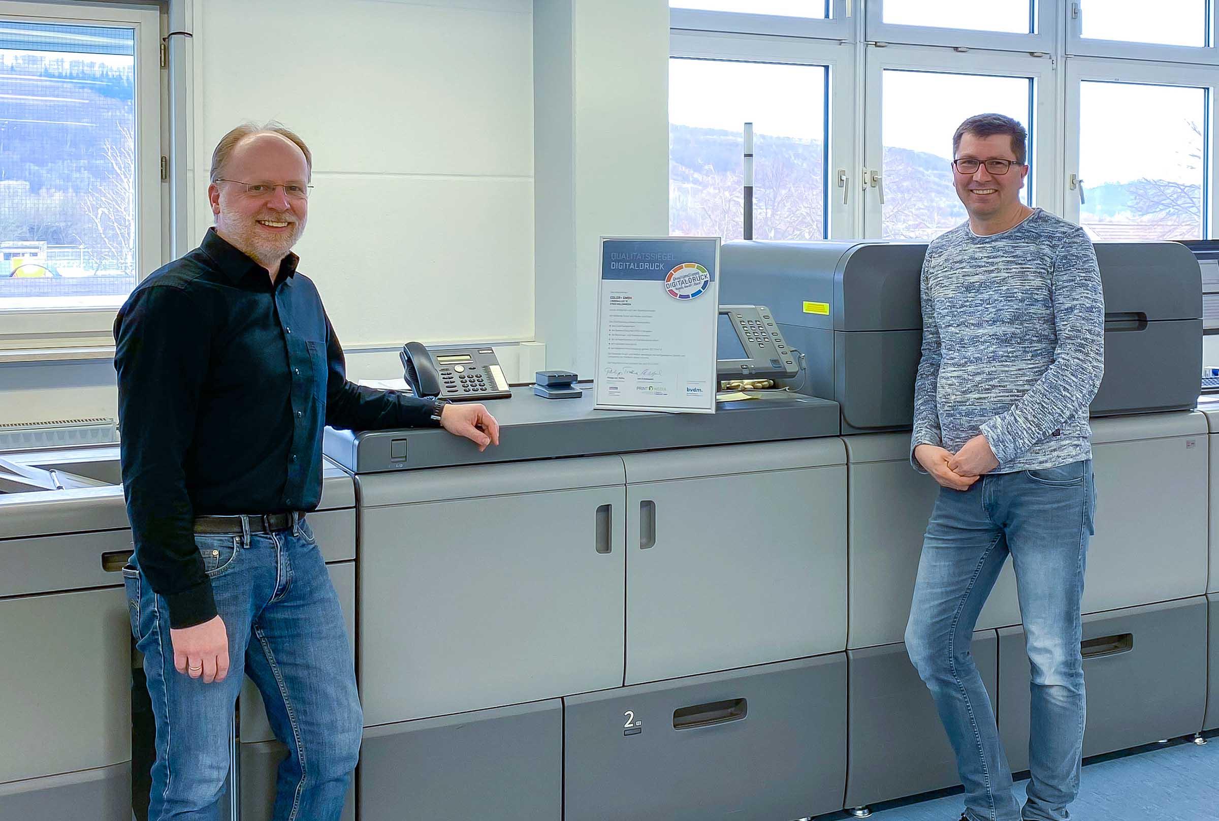 Udo Eickelpasch und Thorsten Stickel von Color+ vor der Digitaldruckmaschine, mit der die Prüfung abgelegt worden ist.